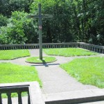 A short set of  stairs lead up to a cross planted on top of the cemetery.